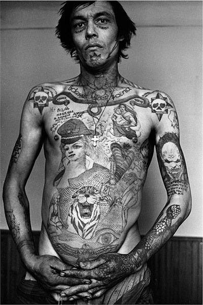 A mono photo-like print of a bare chested man with tattoos